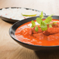 A bowl of chicken tikka masala, as red as red can be, with a dish of rice behind