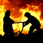 Silhouettes of two firefighters in front of the flames of a fire