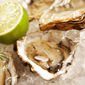 Close-up of open oysters on a bed of ice with lime